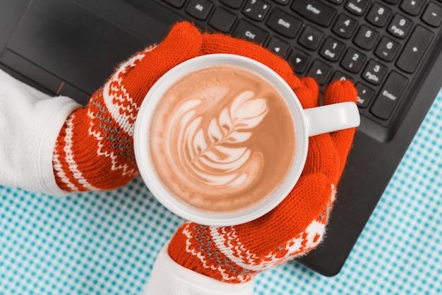 Mãos do teclado do computador em luvas quentes com uma xícara de café de arte
