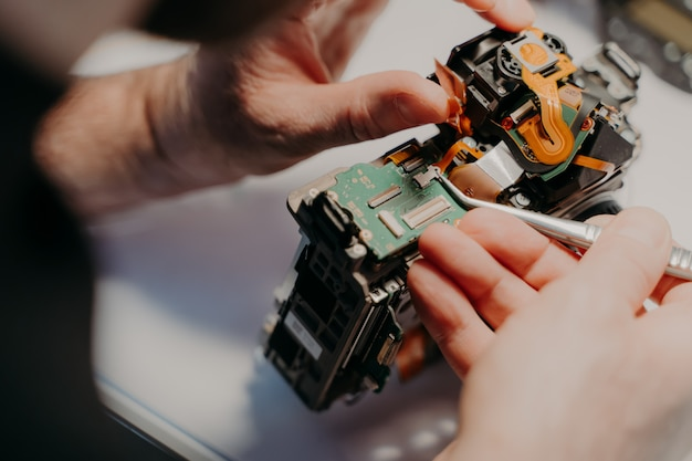 Mãos do trabalhador manual que repara câmera digital quebrada, detém uma pinça especial, trabalha na oficina.