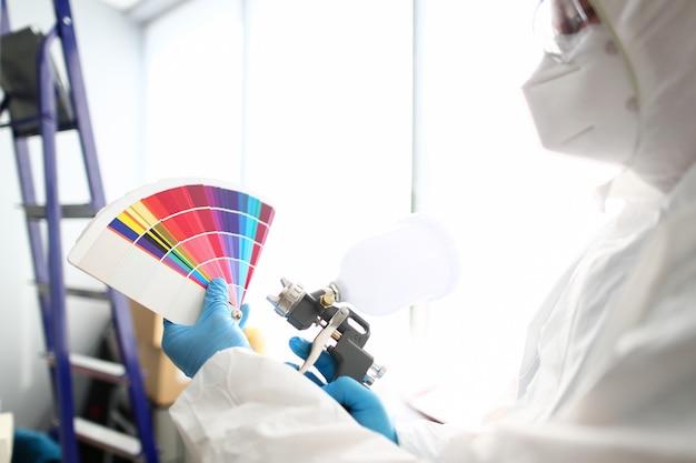 Mãos do trabalhador segurando o aerógrafo e parede de colheita de fantail colorido
