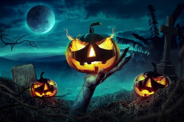 Mãos do zombi que levantam-se na noite escura de halloween.