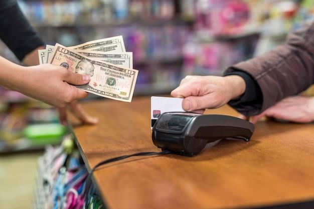 Mãos, dólar e cartão de crédito. conceito de pagamento