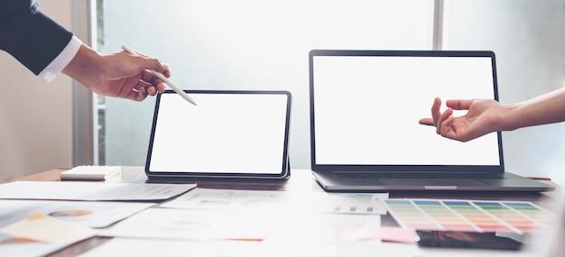 Mãos dos executivos que trabalham no laptop e na tabuleta no escritório criativo.