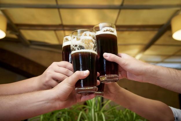 Mãos dos homens com copos de cerveja.