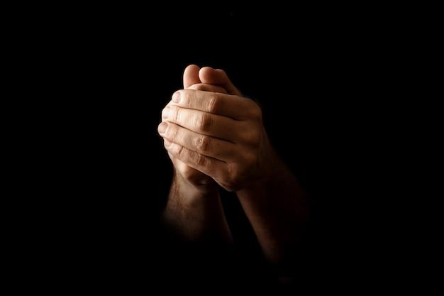 Mãos dos homens em oração