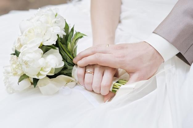 Mãos dos noivos com alianças