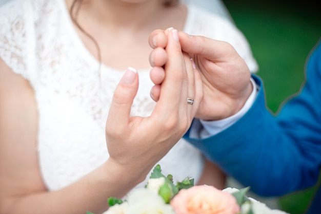 Mãos dos noivos noivos com alianças de ouro
