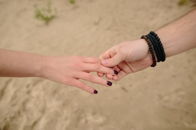 Mãos dos pares no amor, par novo que guarda as mãos no lado de mar em sua lua de mel.
