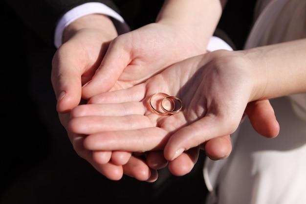 Mãos dos recém-casados com alianças de casamento