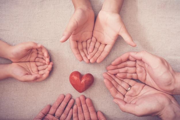 Mãos e coração vermelho, seguro de saúde, conceito de doação e caridade