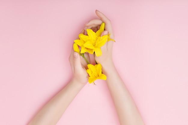 Mãos e flores da primavera estão em um skincare mesa rosa.