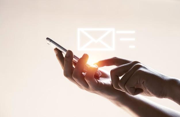Mãos e ícone de carta virtual com telefone celular para enviar e-mail, conceito de tecnologia.