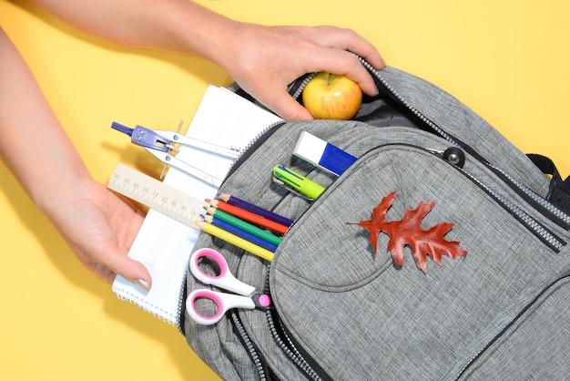 Mãos e mochila com material escolar