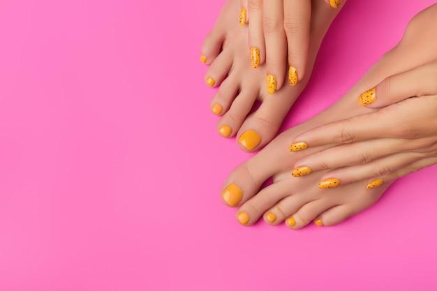 Mãos e pés da mulher em fundo rosa