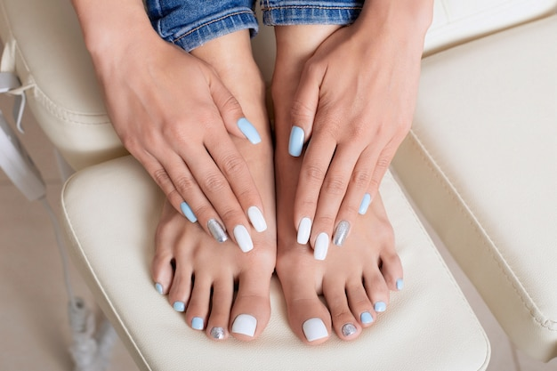 Mãos e pés femininos com unhas de manicure e pedicure, esmalte de gel branco, azul e prata
