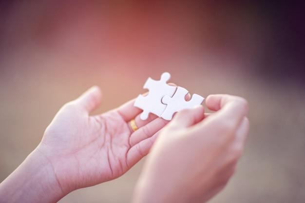 Mãos e quebra-cabeças brancas imagem e integração em close-up conceito e unidade de negócios