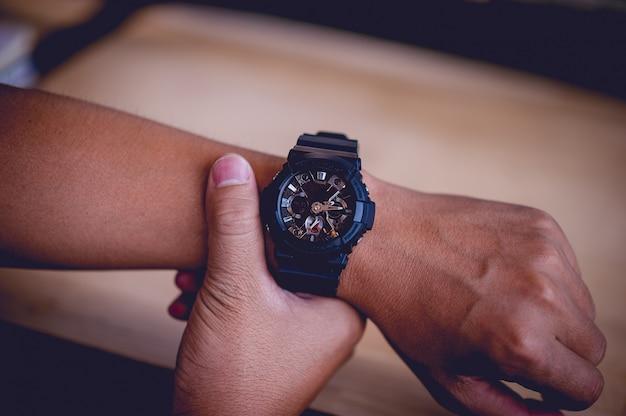 Mãos e relógios de pulso pretos masculinos, conceitos de pontualidade