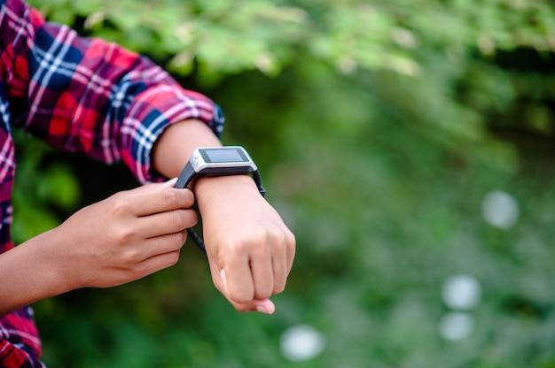 Mãos e relógios digitais de meninos assista a hora no pulso. a orientação é pontual.
