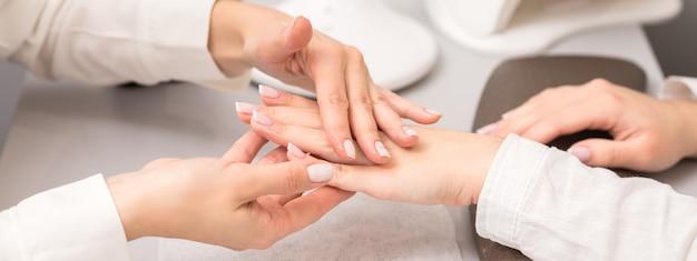 Mãos e unhas de jovem recebendo óleo de massagem por esteticista no salão de beleza.