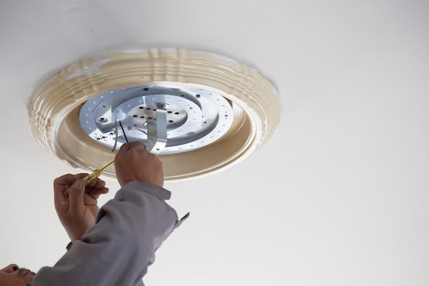 Mãos elétricas que mudam o reparo da lâmpada do teto. conceito de reparação e serviço.