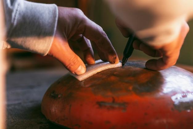 Mãos em close fazendo trabalho artesanal