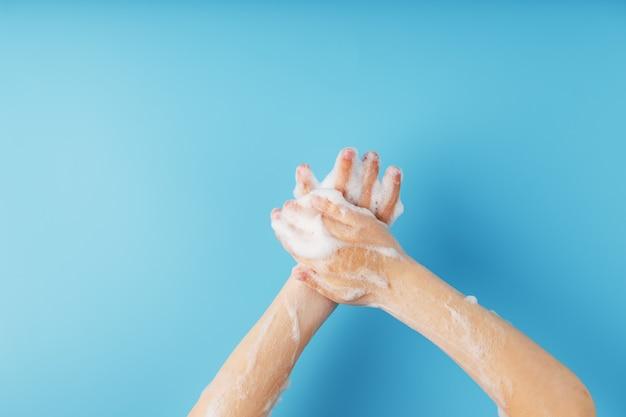 Mãos em espuma de sabão sobre um fundo azul com proteção contra bactérias
