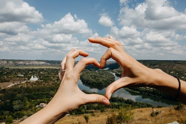 Mãos em forma de coração com vista para o rio drienster.