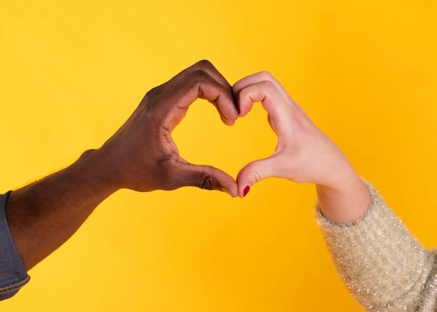 Mãos em forma de coração, mão negra e mão branca, inter-raciais,