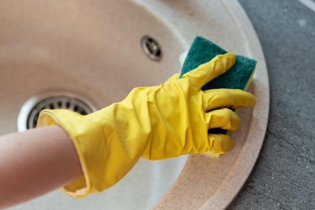 Mãos em luvas amarelas limpando uma pia com uma esponja