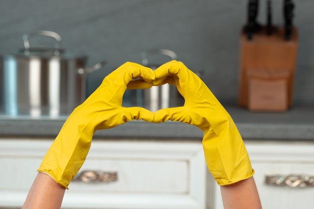 Mãos em luvas amarelas na cozinha