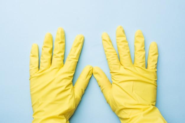 Mãos em luvas amarelas para limpeza em fundo azul.