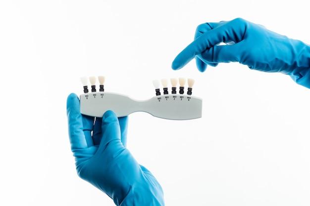 Mãos em luvas azuis segurando paleta de cores dental isolada no fundo branco