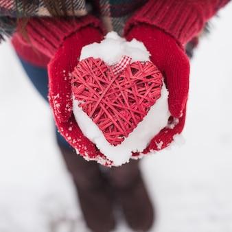 Mãos em luvas de lã segurando um coração vermelho