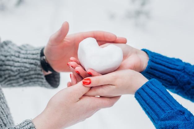 Mãos em luvas de malha com coração de neve em dia de inverno. conceito de amor dia dos namorados.