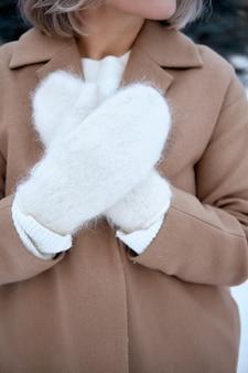 Mãos em luvas de malha. estilo de vida de inverno. vestindo roupas quentes elegantes. mulher em roupas quentes