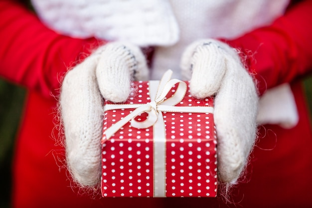 Mãos em luvas de malha, segurando uma caixa de presente de natal artesanal