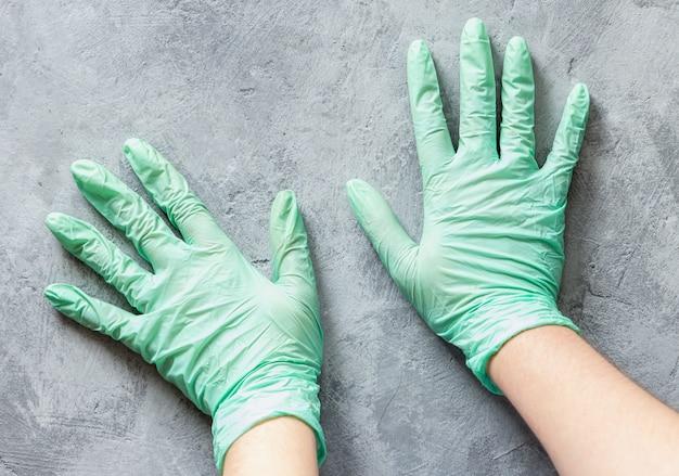 Mãos em luvas de nitrilo verde numa superfície de concreto