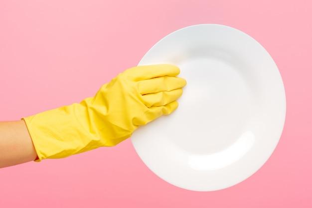 Mãos em luvas de proteção amarelas, lavar um prato