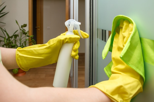 Mãos em luvas de proteção com pano e spray estão limpando o guarda-roupa de vidro
