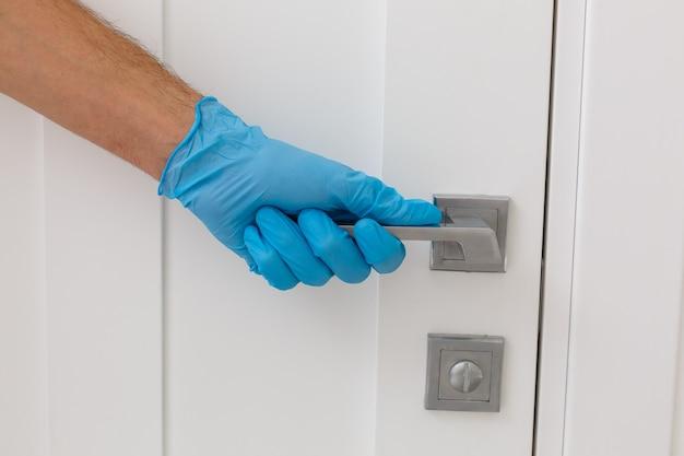 Mãos em luvas de proteção - limpa a maçaneta da porta com um pano umedecido