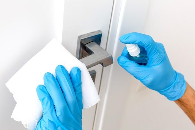 Mãos em luvas de proteção - uma segura o pulverizador com um anti-séptico, a outra - limpa a maçaneta da porta com um pano umedecido com uma solução desinfetante