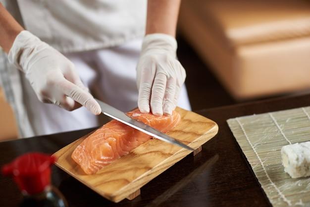 Mãos em luvas descartáveis cortando salmão em uma tábua de madeira