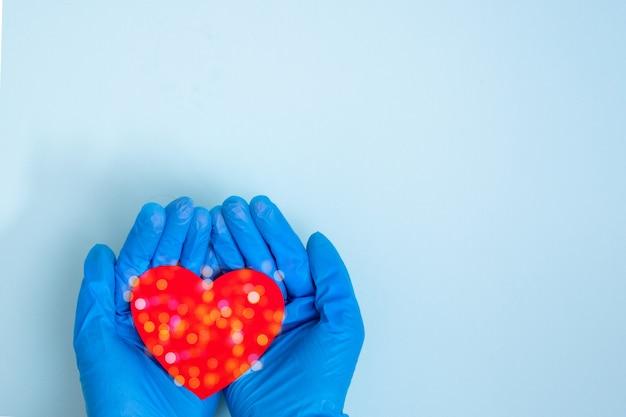 Mãos em luvas médicas azuis segurar um coração vermelho em uma mesa azul, cópia espaço, vista superior. o efeito bokeh é como um floco de neve.