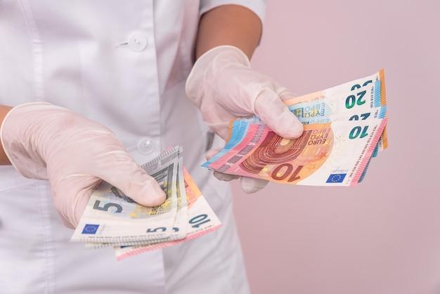 Mãos em luvas médicas com notas de euro