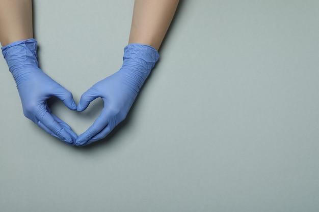 Mãos em luvas médicas mostram coração em cinza claro