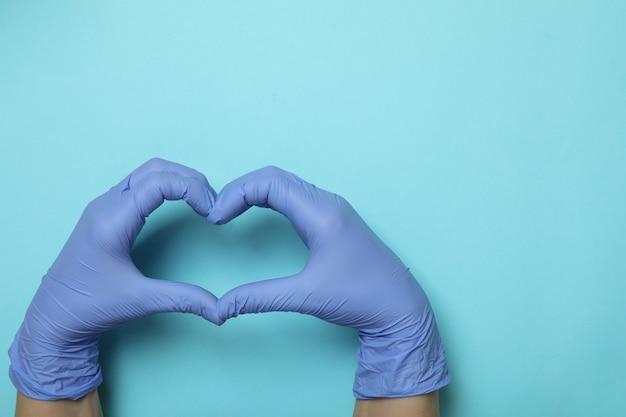 Mãos em luvas médicas mostram coração em fundo azul isolado