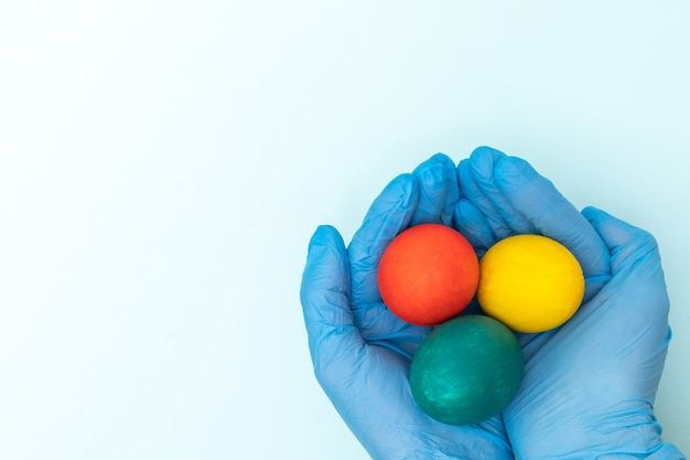 Mãos em luvas médicas protetoras segurando ovos de páscoa coloridos em um fundo branco