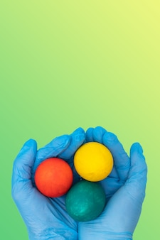 Mãos em luvas médicas protetoras segurando ovos de páscoa coloridos em um fundo gradiente verde-amarelo primavera
