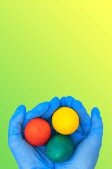 Mãos em luvas médicas protetoras segurando ovos de páscoa coloridos em uma superfície verde-amarela de primavera gradiente. conceito de feliz páscoa seguro.