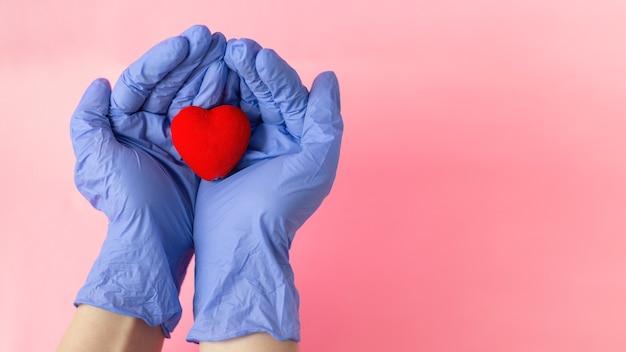 Mãos em luvas médicas seguram o coração