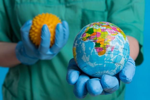Mãos em luvas médicas seguram uma maquete do planeta terra em primeiro plano e uma maquete do vírus, símbolo da pandemia global, o conceito